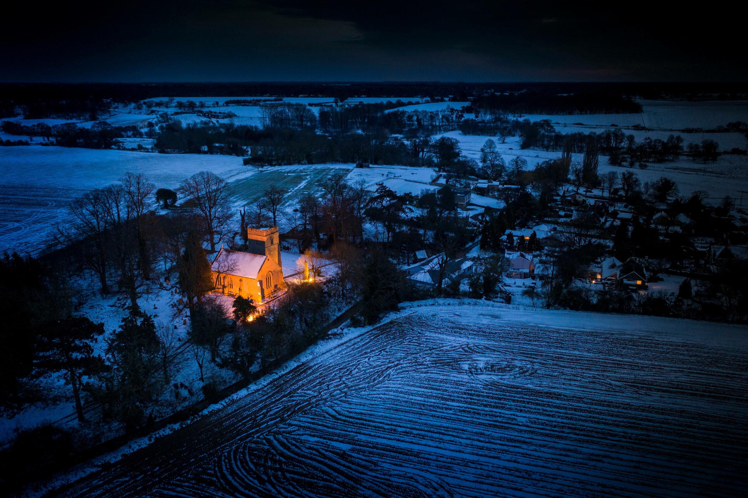 Playford Church illuminated in the winter night
